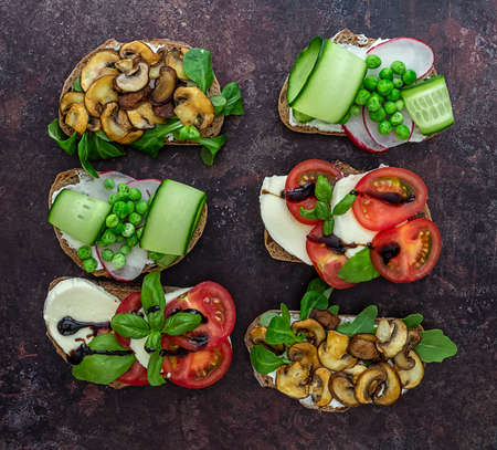Open vegetarian toasts with different toppings, top view. Flat lay of rye bread crostini with mushrooms, tomatoes, cucumbers.