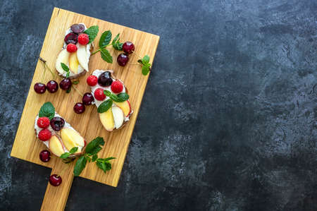 Healthy summer toasts for breakfast. Rye bread topped ricotta, berries, and peach. Copy space, top view. 版權商用圖片