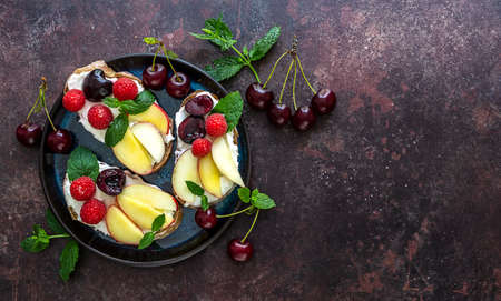 Sweet toasts for healthy breakfast with ricotta, fresh peach, and berries. Copy space, top view. 版權商用圖片