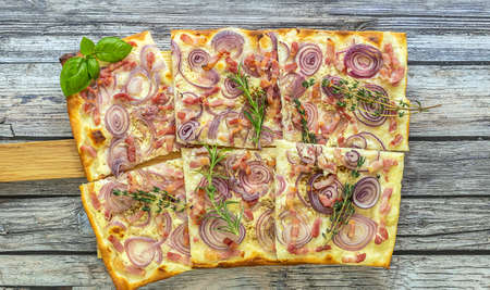 Traditional german pizza or flammkuchen - open tart with beacon, red onion, and fresh cream.