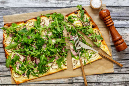 Flammkuchen - Traditional German pizza or french tarte flambee in vegetarian recipe with mushrooms, cream cheese, onion, and arugula.