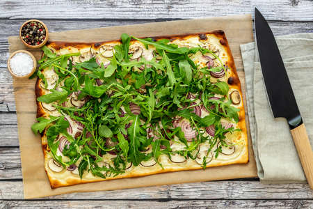 Fresh baked flammkuchen - Traditional German pizza or french tarte flambee in a vegetarian recipe with mushrooms, cream cheese, onion, and arugula.