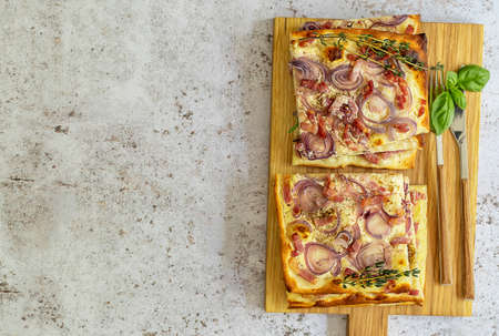 Traditional sliced german pizza or flammkuchen - open tart with bacon, red onion, and fresh cream. Copy space for recipe or text. 版權商用圖片