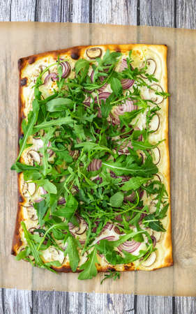 The vertical orientation of freshly baked flammkuchen - Traditional German pizza or french Tarte flambee in a vegetarian recipe with mushrooms, cream cheese, onion, and arugula.