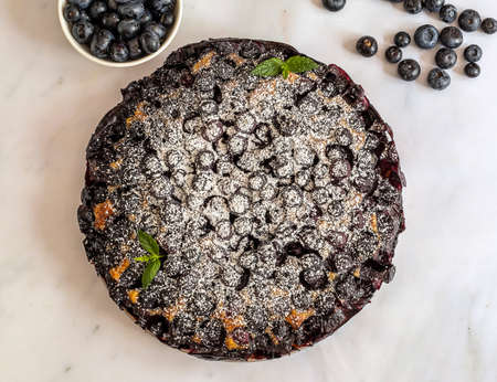 Homemade fresh-baked blueberry pie covered sugar powder, flat lay.