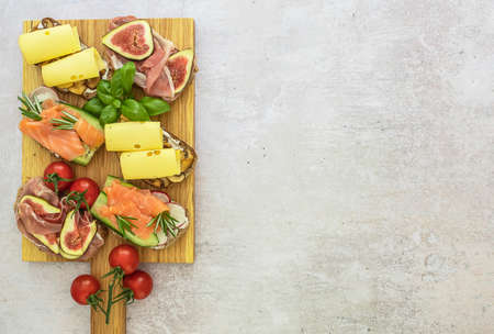The assortment of homemade toast sandwiches with salmon, ham, and cheese on wooden board. Healthy snacks concept, copy space.