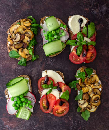 Vegetarian sandwich toasts with different toppings, top view. Flat lay of rye bread crostini with mushrooms, tomatoes, cucumbers. 版權商用圖片