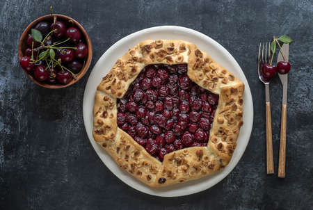Sour cherry open pie or galette with cutlery and fresh berries.