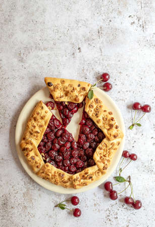 Vertical orientation of cut piece sour cherry pie galette. Summer baking concept with copy space.