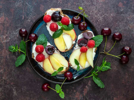 Healthy summer sweet toasts for breakfast. Rye bread topped ricotta, berries, and peach. 版權商用圖片