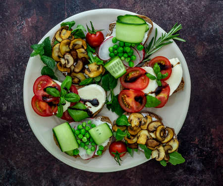 Plate with vegetarian sandwich toasts with different toppings, top view. Flat lay of rye bread crostini with mushrooms, tomatoes, cucumbers.