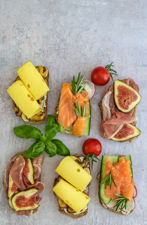 The vertical orientation of healthy snacks. Homemade toast sandwich with salmon, ham, and cheese. 版權商用圖片
