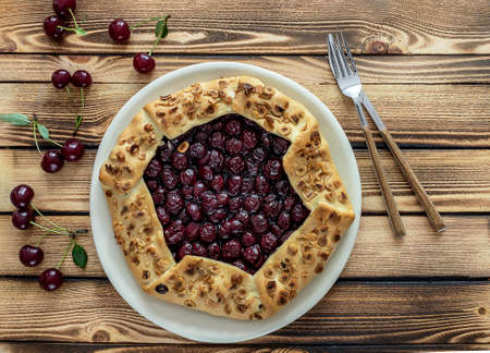 Sour cherry open pie or galette with cutlery and fresh berries on a wooden table.