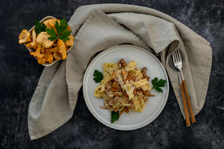Italian pasta Tagliatelle with chanterelle mushrooms in a white plate with napkin and cutlery.
