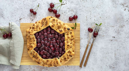Top view of sour cherry open tart or galette with cutlery and fresh berries. Copy space for recipe or text.