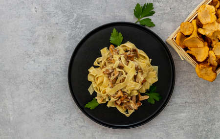 Italian pasta Tagliatelle with chanterelle mushrooms and parsley in a black plate with copy space for recipe or text