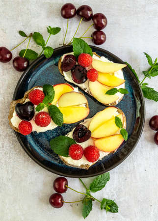 Delicious french toast with fresh fruits, berries, and honey. Tasty breakfast scene or dessert with bread, raspberries, cherries, peach, and ricotta. vertical orientation