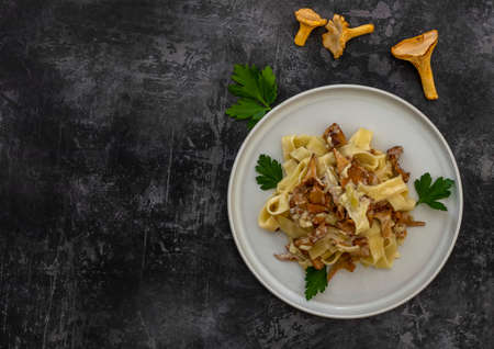 Top view of Italian pasta Tagliatelle with chanterelle mushrooms and parsley in a white plate with copy space for recipe or text