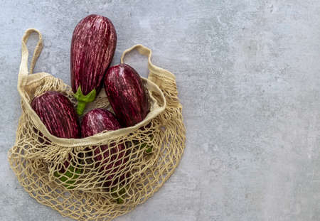 Textile string bag with ripe organic eggplants. No plastic zero waste shopping concept. 版權商用圖片