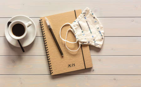 Planner for 2021. Notebook and mask on the wooden table with cup of coffee. Top view, flat lay on wooden table.