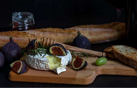 Mouthwatering oven baked Camembert cheese with berries, honey, figs