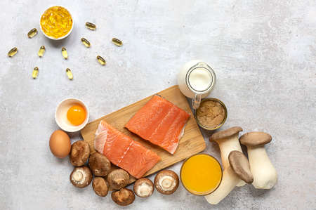 Flat lay composition with products rich in vitamin D. Canned tuna, mushrooms, salmon, eggs, milk, and orange juice - great natural sources of vitamin D.