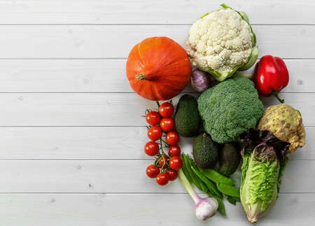Healthy food background, trendy plant based diet products - fresh raw vegetables. natural wooden surface, copy space