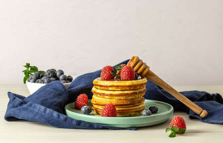 Tasty american pancakes with raspberries, blueberries, and honey. Breakfast concept with copy space.