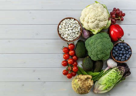 Healthy food background, trendy plant based diet products - fresh raw vegetables, fruits, and beans. natural wooden table, copy space Stock Photo