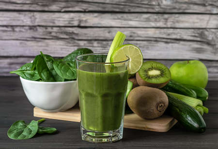 Glass of fresh organic green smoothie with spinach, cucumber, kiwi, celery, and avocado on wooden background. Healthy diet concept.