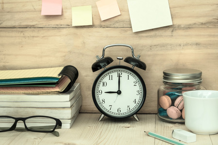 office time: books , glasses, clock ,macaroons and a cup of coffee on workplace desktop