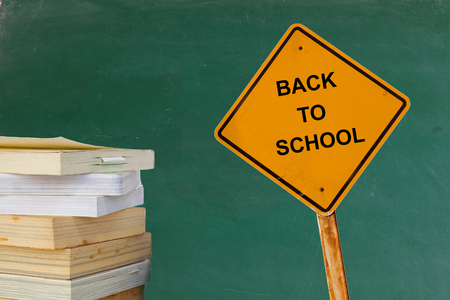 final examination: stack of books and yellow traffic sign with text BACK TO SCHOOL on blackboard background Stock Photo