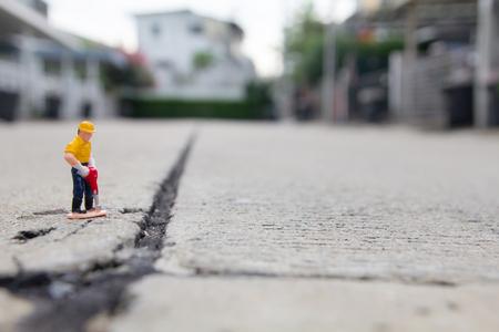 kleine figuur van een man graven betonweg