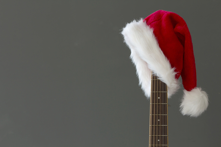 Red Christmas hat on guitar with grey background, Merry Christmas