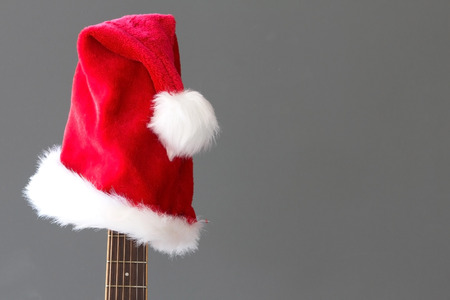 holiday music: Red Christmas hat on guitar with grey background, Merry Christmas