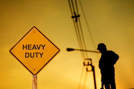 duty: warning sign message HEAVY DUTY with silhouette of construction worker.