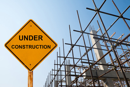 house under construction: house structure with message under construction. Stock Photo