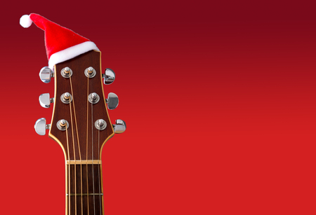 Red Christmas hat on guitar with red background, Merry Christmas song
