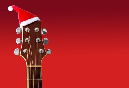 Sombrero rojo de Navidad en la guitarra con fondo rojo, canción Feliz Navidad
