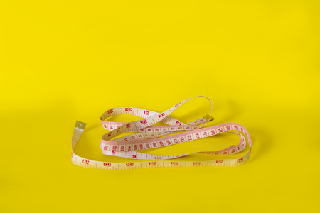 body measurement tape isolated on yellow minimal style photo