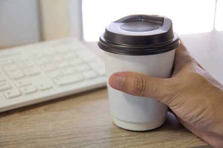 hand of office man holding a cup of coffee in the morning