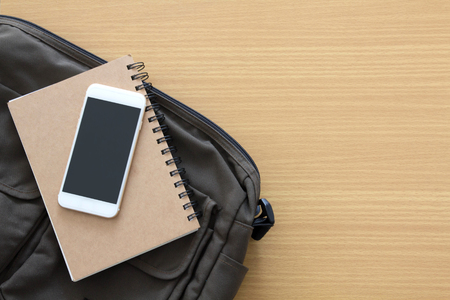 student bag with books and mobile phone