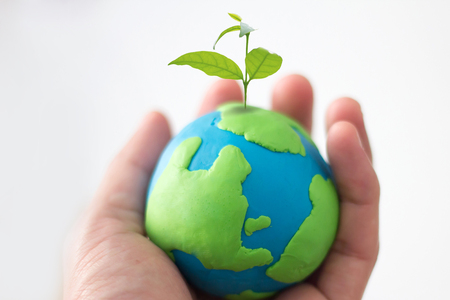 Globe on hand with plant, safe the world , CSR Abbreviation or Corporate Social Responsibility concept