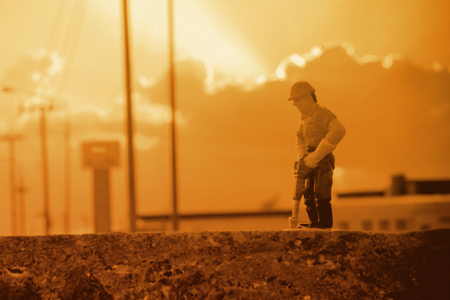 small figure of a man digging concrete street with Work in Progress concept.
