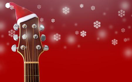 Rode Kerstmishoed op gitaar met sneeuw en rode achtergrond, Vrolijk Kerstmislied Stockfoto - 89406183
