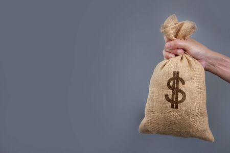 hand holding money bag , salary payment and saving money  concept