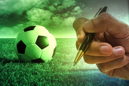 Football with football player hand to sign contract , soccer journalist Фото со стока