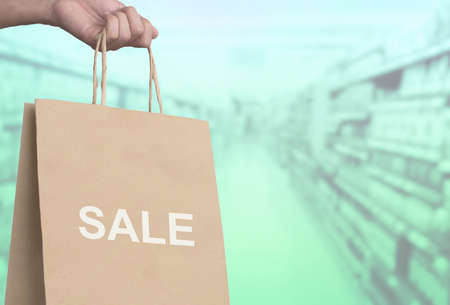 hand holding shopping bag with message SALE , shopping sale concept 写真素材
