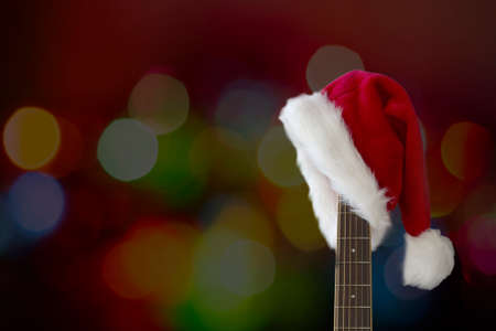 Red Christmas hat on guitar with light bokeh background, Merry Christmas song