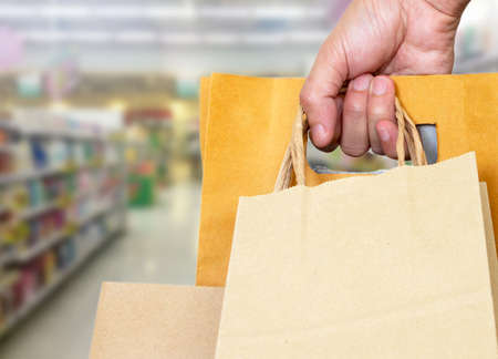 hand holding shopping bag with blur image of supermarket , shopping concept